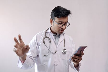 male indian doctor in white coat and stethoscope in worried expression while looking at smart phone