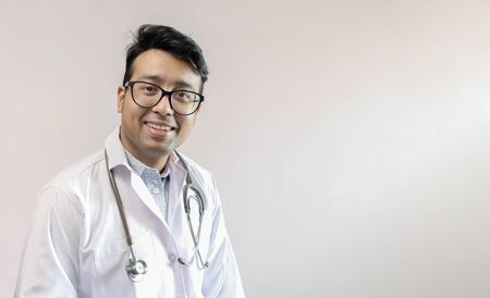 male indian doctor in white coat and stethoscope with space for text in white background
