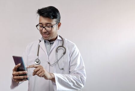 male indian doctor in white coat and stethoscope touching smart phone