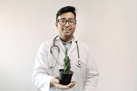 male indian doctor in white coat and stethoscope with a cactus plant on a pot