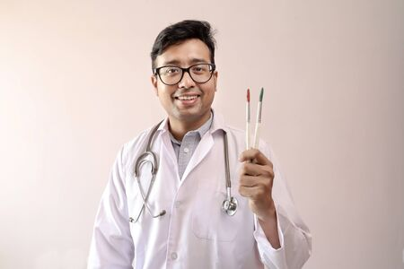 male indian doctor in white coat and stethoscope with paint brush
