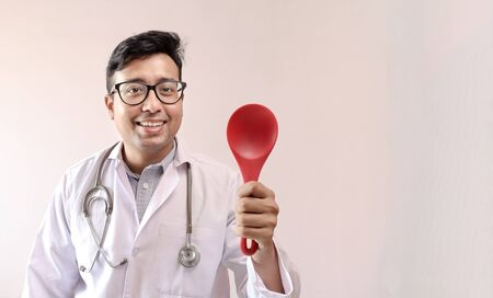 male indian doctor in white coat and stethoscope and cooking ladle