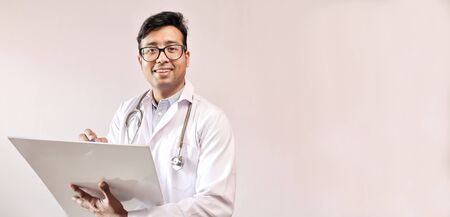 male indian doctor in white coat and stethoscope writing notes and prescribing medicine Imagens