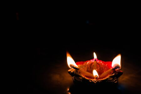 earthen oil lamp lit on the occasion of deepavali, a hindu festival of light with selective focus on lamp and background and foreground blur