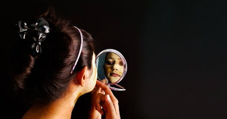 an indian lady with face pack applied in half dried condition checking her face in a mirror with selective focus on the mirror image