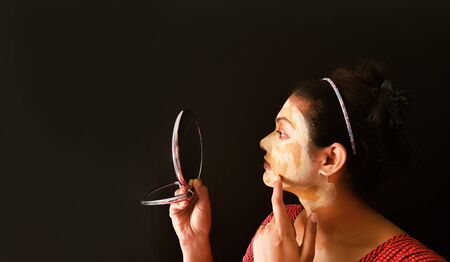 an indian lady with face pack applied in half dried condition checking her face in a mirror