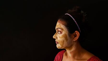 an indian lady with face pack applied in half dried condition. side view of face Banco de Imagens