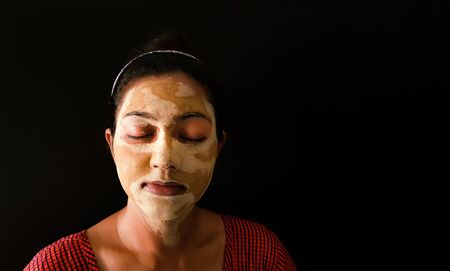 an indian lady with face pack applied in half dried condition with eyes closed front view Banco de Imagens