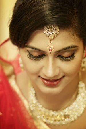 Atemberaubende indische Braut, gekleidet in hinduroter traditioneller Hochzeitskleidung, Sari, bestickt mit Goldschmuck und einem Schleier, lächelt zart mit zusätzlichem Kopierraum.