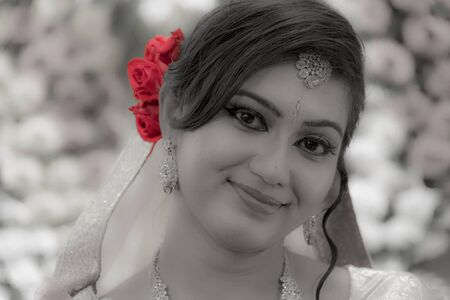 a beautiful young indian bride in bridal makeup with eyes at the camera in black and white with selective red colored rose Banco de Imagens