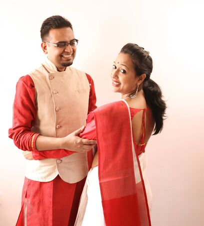 a young indian bengali assamese married romantic couple dressed in red and white ethnic indian dress, looking at each other and smiling Banco de Imagens