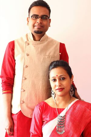 a young indian bengali assamese married couple dressed in red and white ethnic indian dress