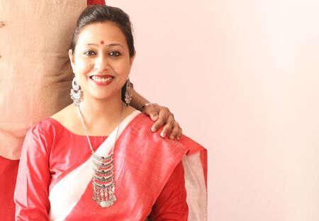 a young indian bengali assamese married lady dressed in red and white saree and smiling