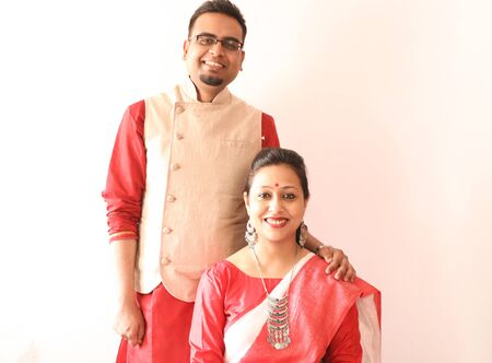 a young indian bengali assamese married couple dressed in red and white ethnic indian dress and smiling