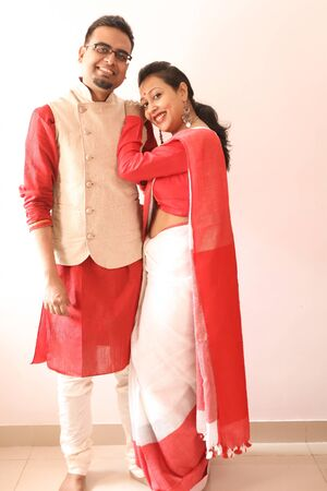 a young indian bengali assamese married romantic couple dressed in red and white ethnic indian dress, looking at the camera and smiling Banco de Imagens
