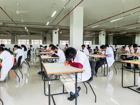 October 30, 2019, Kolkata, India. Medical students writing a medical examination in examination hall wearing white coats during day time at NRS Medical College Kolkata, India.