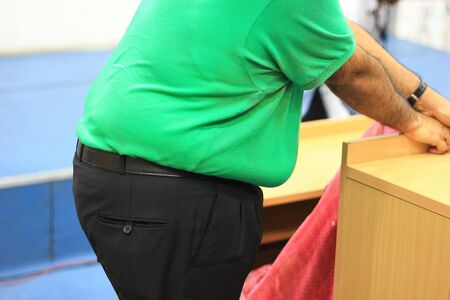 side view of a large tummy of a morbid obese person without face in green t-shirt and black trousers Stock fotó