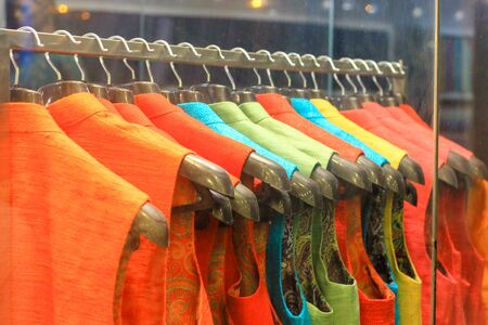 indian bridal ethnic wear kurta hanging from hangar at a shop for sale behind glass Stock Photo
