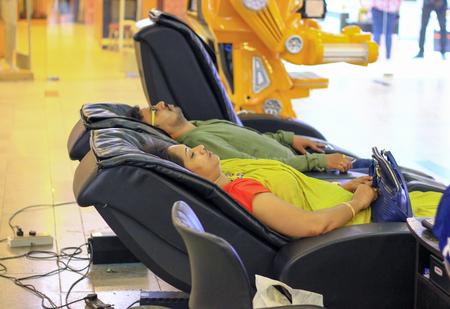 16 November, 2019. - Kolkata,India. Bengali housewife and husband relaxing on massage chair after days work at a mall, Kolkata, India
