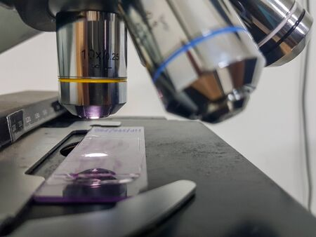 close up view of a light microscope with glass slide focussed Banco de Imagens