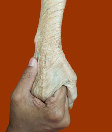 Hand of an elderly holding the hand of a young, elderly support concept in orange background