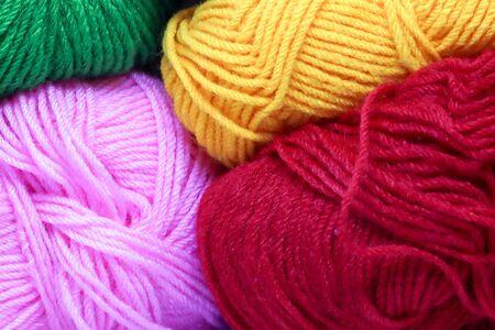 pelotes de laine de couleur rose vert rouge jaune et blanc.