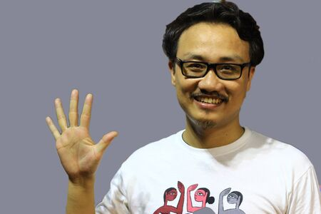 A smiling and confident manipuri north east indian man with spectacles showing the sign of five with fingers