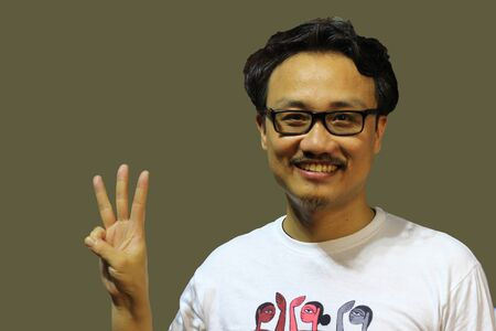 A smiling and confident manipuri north east indian man with spectacles showing the sign of three with fingers