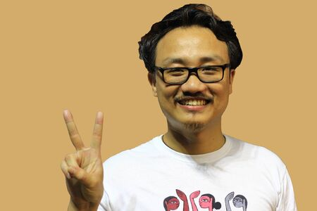 A smiling and confident manipuri north east indian man with spectacles showing the sign of two and victory with fingers