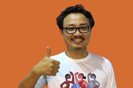 A smiling and confident manipuri north east indian man with spectacles showing the sign of one and thumbs up with fingers Reklamní fotografie - 135499802
