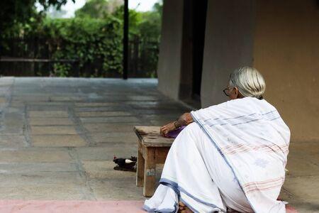 November 30, Maharashtra India,- An elderly lady in white dress reading books in the evening at Gandhi Ashram at Sevagram, Wardha. Mahatma Gandhi used to reside there Sajtókép