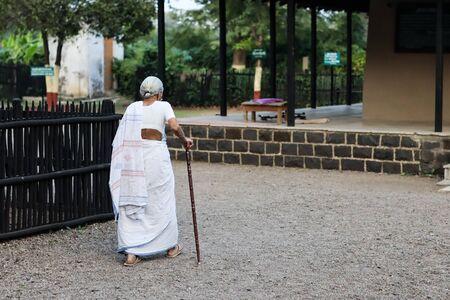 November 30, Maharashtra India,- An elderly lady with walking stick in white dress walking at Gandhi Ashram at Sevagram, Wardha. Mahatma Gandhi used to reside there