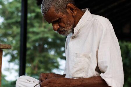 November 30, Maharashtra India,- An elderly man in white dress sweing cloth at Gandhi Ashram at Sevagram, Wardha. Mahatma Gandhi used to reside there
