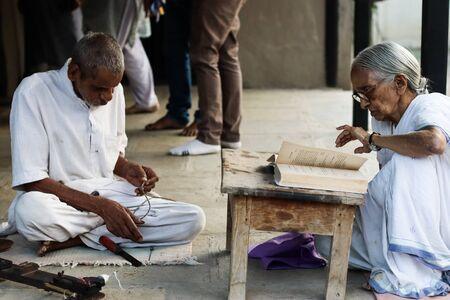 November 30, Maharashtra India,- An elderly man and lady lady in white dress reading books and sewing cloths at evening at Gandhi Ashram at Sevagram, Wardha Sajtókép