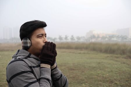 a man feeling cold being dressed in winter garments and gloves with focus on models face with a foggy haze in the background