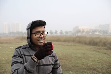 a man drinking hot coffee from a red cup and dressed in winter garments and gloves with focus on models face with a foggy haze in the background
