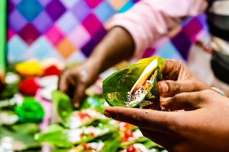 hand of a seller holding fire paan, betel leaf on flame.