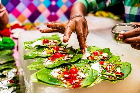 a hand sprinkling pan masala garnish and cherry on betel leaf during preparation of banarasi pan. Reklamní fotografie