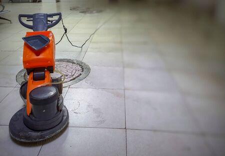 un limpiador de pisos motorizado con fregona sobre piso de mármol de granito blanco con fondo borroso.
