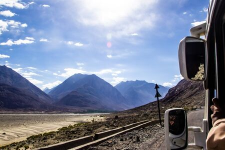 view of roads of ladakh kashmir from car window while travelling in a car with hills and blue sky.