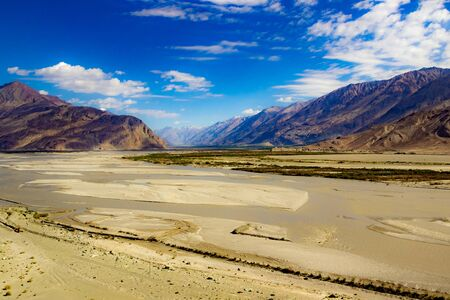 High dynamic range image of barren mountain in a desert with river and deep blue sky and white patchy clouds in ladakh, Jammu and Kashmir, India
