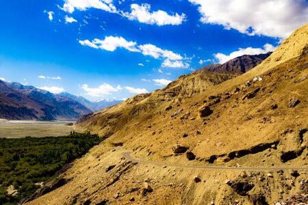 curved hilly highway in between barren himalayan mountains of leh ladakh, jammu and kashmir, India