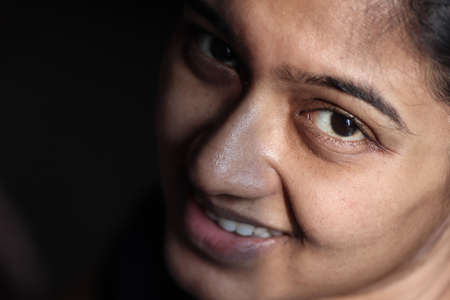 closeup portrait of a lady with light on half of her face with expressive eyes selective focus on front eye giving a hopeful delighted expression.