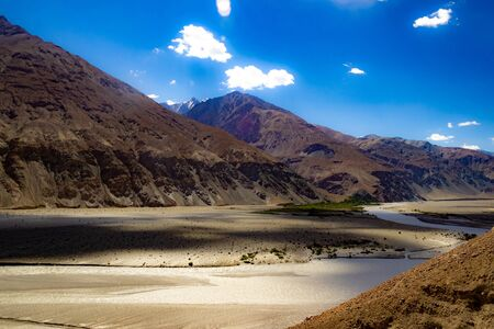shades of cloud in High dynamic range image of barren mountain in a desert with river and deep blue sky in ladakh, Jammu and Kashmir, India