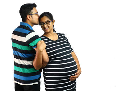 a young couple showing a pregnant lady in satisfied content expression with her husband kissing ger head in white background with copy for text.