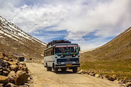 Ladakh,India. 26-June 2016 - A public bus driving in rocky highway surrounded by himalayan mountain during the day at ladakh, Kashmir, India.