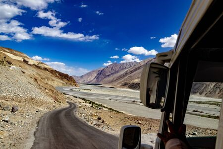 view of a curved road along barren dry himalayan hills of ladakh. travel photography concept with parts of car in foreground Reklamní fotografie