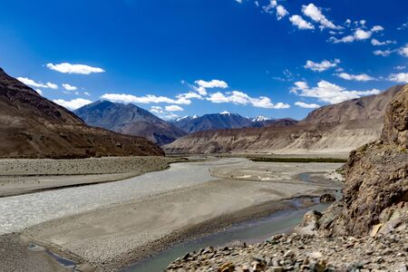 curved driving road high way and landscape showing vivid deep blue sky with foreground of rocky pebbles and barren dry mountains of ladakh, Kashmir