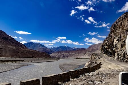 curved driving road high way and landscape showing vivid deep blue sky with foreground of rocky pebbles and barren dry mountains of ladakh, Kashmir Reklamní fotografie