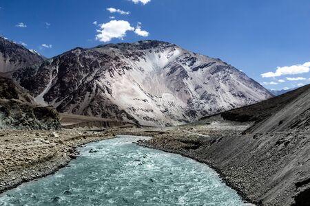 vivid landscape showing origin of a river at the base of a glacier with deep blue sky and snow capped barren himalayas of leh, kashmir, India. Reklamní fotografie